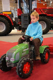 Boy astride  small tractor Stock Photos