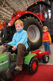 Boy astride small tractor, girl standing behind Stock Photos