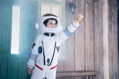 Boy in astronaut costume flying on porch Stock Image