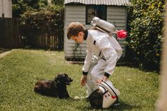 Boy in astronaut suit playing with his dog stock images