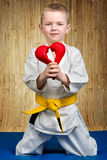 The boy athlete karate gives heart,Declaration of love ,sympathy .Karate on the Mat in the gym. Karate on the Mat in the gym royalty free stock photo