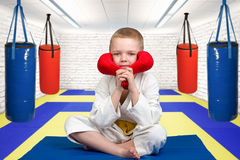 The boy athlete karate sitting in the gym with gloves on.Karate on the Mat in the gym. Karate on the Mat in the gym stock image