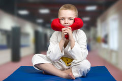 The boy athlete karate sitting in the gym with gloves on.Karate on the Mat in the gym. Karate on the Mat in the gym.little athlete royalty free stock image