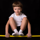 Boy athlete performs exercises with gymnastic stick in the gym Royalty Free Stock Photo
