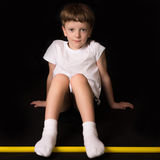 Boy athlete performs exercises with gymnastic stick in the gym Stock Photography