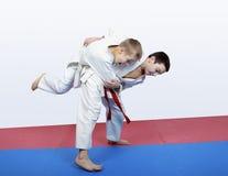 Boy athlete with a red sash makes hip throw Royalty Free Stock Photo