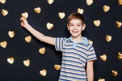 Boy attaching gold heart on dark background Stock Photos