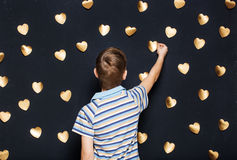 Boy attaching gold hearts on dark background Royalty Free Stock Photos