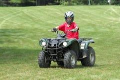 Boy on ATV. Young boy riding four-wheeler ATV Royalty Free Stock Photo