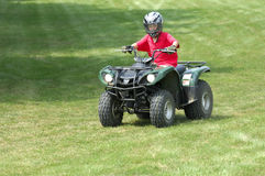 Boy on ATV. Young boy riding four-wheeler ATV Royalty Free Stock Photos