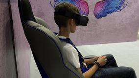 Boy in augmented reality glasses on virtual reality chair. Teenager in augmented reality glasses siting on virtual reality chair and looking to virtual show stock video footage