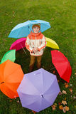 Boy in autumn park, in environment of umbrellas Royalty Free Stock Images