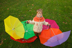 Boy in autumn park, in environment of umbrellas Royalty Free Stock Photo