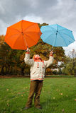Boy in autumn park. Holds over head two umbrellas Stock Photography