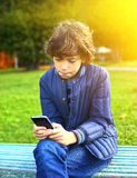 Boy in the autumn park play computer game Royalty Free Stock Photos