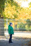 A boy plays in the autumn on the street. A boy in the autumn playing on the street smiling on a sunny day Royalty Free Stock Photography