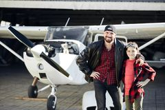Boy in aviator glasses stands with his dad, wants to be a pilot too. Boy in aviator glasses stands wih his dad, proud of his father pilot, wants to be like him royalty free stock photography