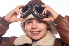 The boy is an aviator in the jacket of the pilot and in old glasses royalty free stock photo