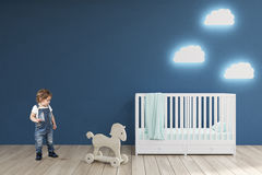 Boy in a baby's room, blue walls. Little boy in a baby's room with a crib, cloud shaped lamps and a toy horse. Blue walls. Concept of minimalism. 3d Royalty Free Stock Images