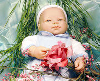 Boy Baby Doll. With artificial flowers and foliage Stock Image