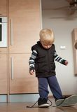 Boy. Baby boy funny wearing big shoes in living room Royalty Free Stock Photos