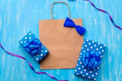Boy baby shower card template. Aged paper-bag to insert your text, blue bow. Dotted gift boxes, violet and blue ribbons, a handmade paper bow on the blue royalty free stock photography