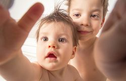 Boy and baby with wet hair taking selfie photo Stock Photos