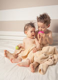 Boy and baby with wet hair under towels playing Royalty Free Stock Image
