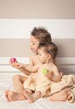 Boy and baby with wet hair under towels playing Royalty Free Stock Images