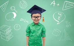Boy in bachelor hat and eyeglasses over blackboard. Childhood, school, education, knowledge and people concept - happy boy in bachelor hat or mortarboard and Stock Photo