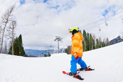 Boy from the back in ski mask and helmet skiing Stock Photo