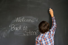 Boy and back to school black board. Boy drawing back to school black board in background Stock Images