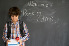 Boy and back to school black board. Teenage Boy with backpack, books and apple with back to school on black board background Stock Photography