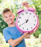 Boy back to school. Outdoor portrait of happy teen boy 12-14 year old with big alarm clock. Back to school concept. Beautiful schoolboy posing outdoors. Young Royalty Free Stock Photo