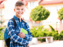 Boy back to school. Outdoor portrait of happy teen boy 12-14 years old with books and backpack. Young student beginning of class after vacation. Back to school Stock Photography