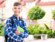 Boy back to school. Outdoor portrait of happy teen boy 12-14 years old with books and backpack. Young student beginning of class after vacation. Back to school Royalty Free Stock Images