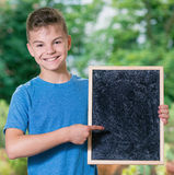 Boy back to school. Outdoor portrait of happy teen boy 12-14 years old with small blackboard. Back to school concept. Young student beginning of class after Royalty Free Stock Photography