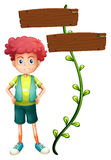 A boy at the back of a two-plank wooden signage Royalty Free Stock Image