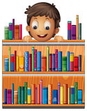 A boy at the back of a wooden shelves with books Royalty Free Stock Photos