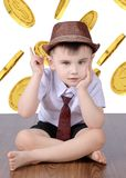 Boy on the background of coins royalty free stock photography