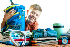 Boy on the background of his things with a bag royalty free stock image