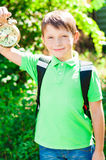 Boy with a backpack and a clock in hands Stock Image