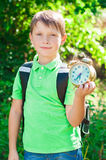 Boy with a backpack and a clock in hands Royalty Free Stock Image