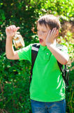 Boy with a backpack and a clock in hands Royalty Free Stock Photography