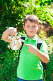 Boy with a backpack and a clock in hands Stock Photo