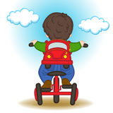 Boy with backpack in form of car rides bicycle Royalty Free Stock Images