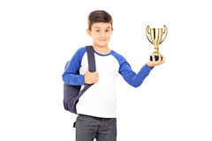 Boy with backpack holding a trophy Stock Photo