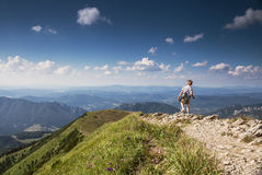 Boy with backpack on mountain hill foot pathe Stock Photos