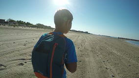 A boy with a backpack running along the sea shore stock video footage