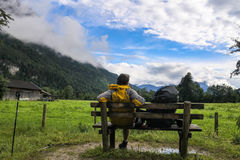 Boy with backpack sitting on bench in the middle of mountains bavarian Germany Alps in front of beautiful green field view fog on Royalty Free Stock Photography